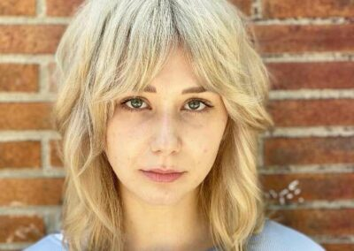 Person with blonde hair and bangs.