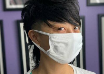 Person with styled, dark hair, wearing a mask.