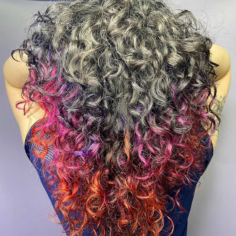 Close-up photo of a silver, pink, and orange gradient dye on a curly-haired client